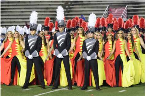 The drum majors and flag team stand in formation awaiting awards at the Bands of America marching band competition.