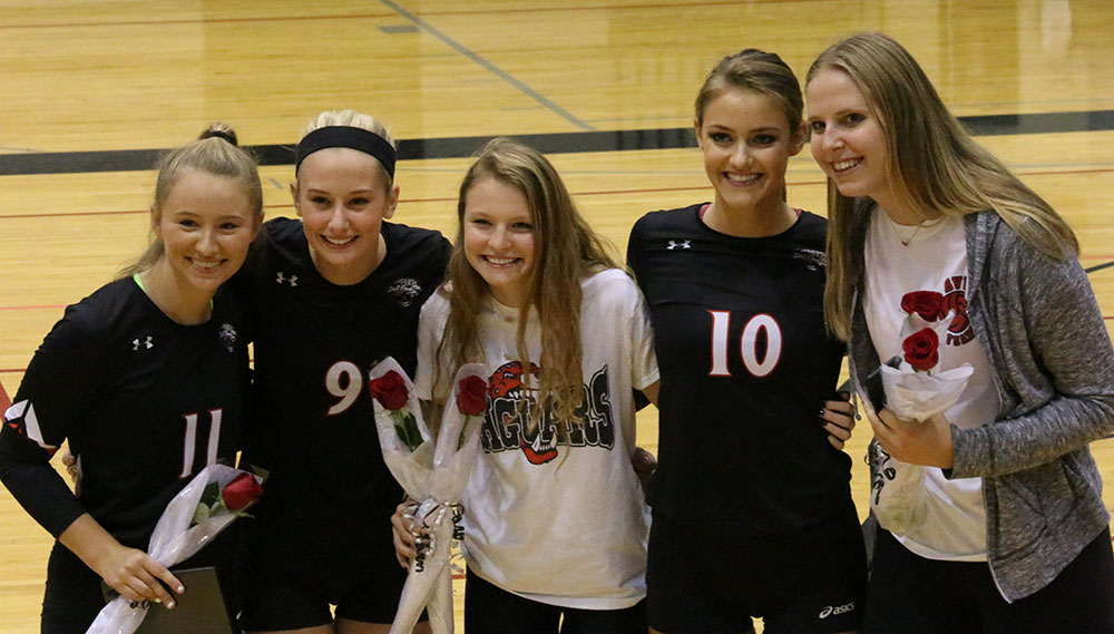 Senior volleyball players and their managers Annie Dykstra and Hanna Fisher, pose together on volleyball's Senior Night