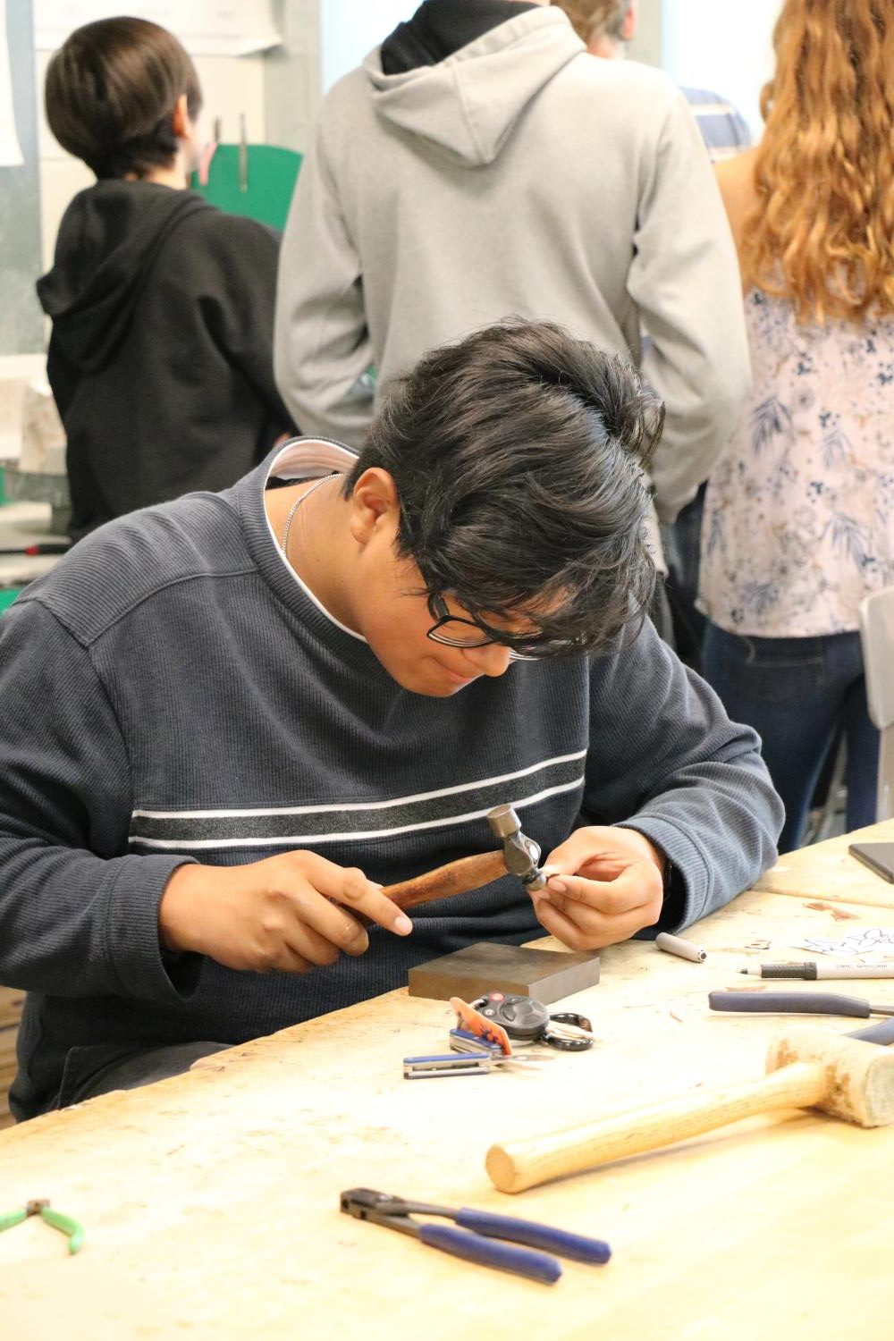 Junior Tanner Rupp works diligently in Jewelry 1 to create his artwork. Students begin with simpler machinery and work their way up.