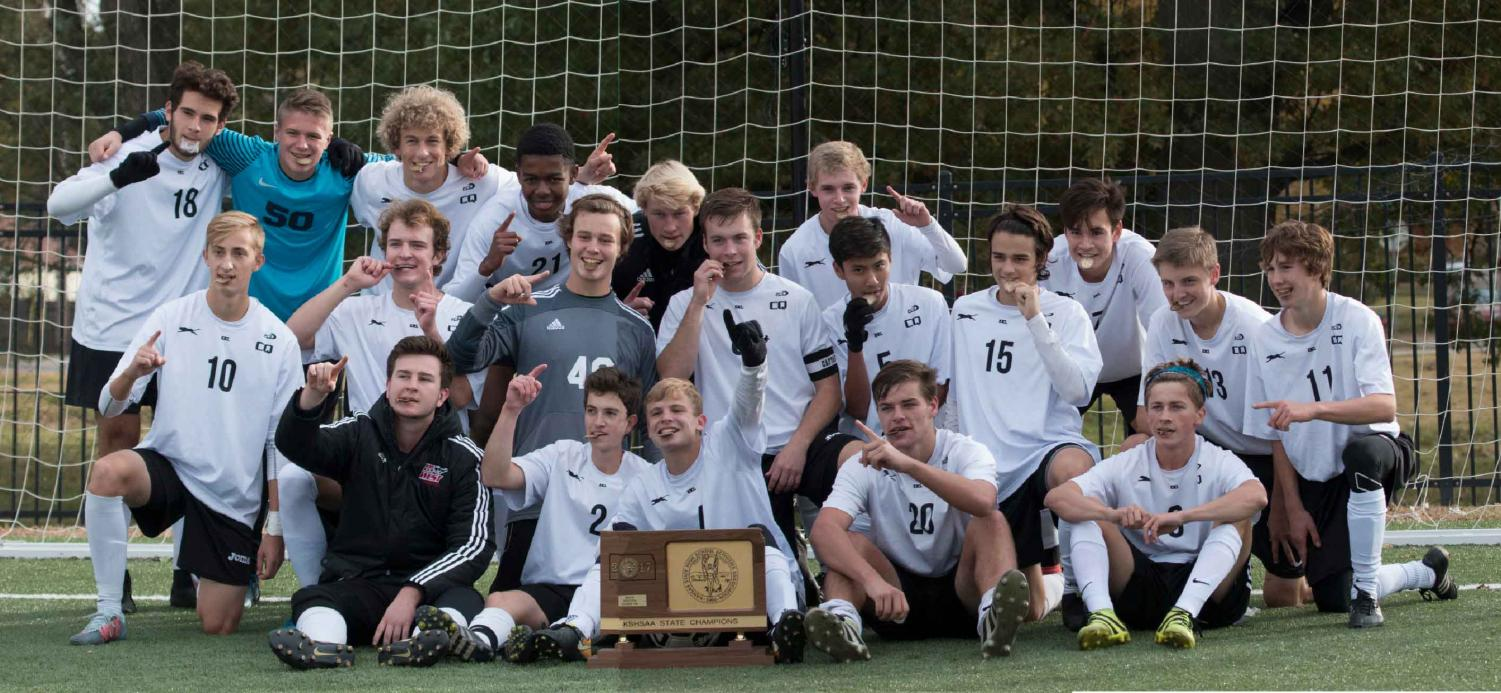 STATE CHAMPS! The boys soccer team poses with their trophy and medals after capturing the KSHSAA 6A State Championships over Olathe South on Nov. 4 at the Hummer Sports Complex in Topeka. The final score was 3-1.