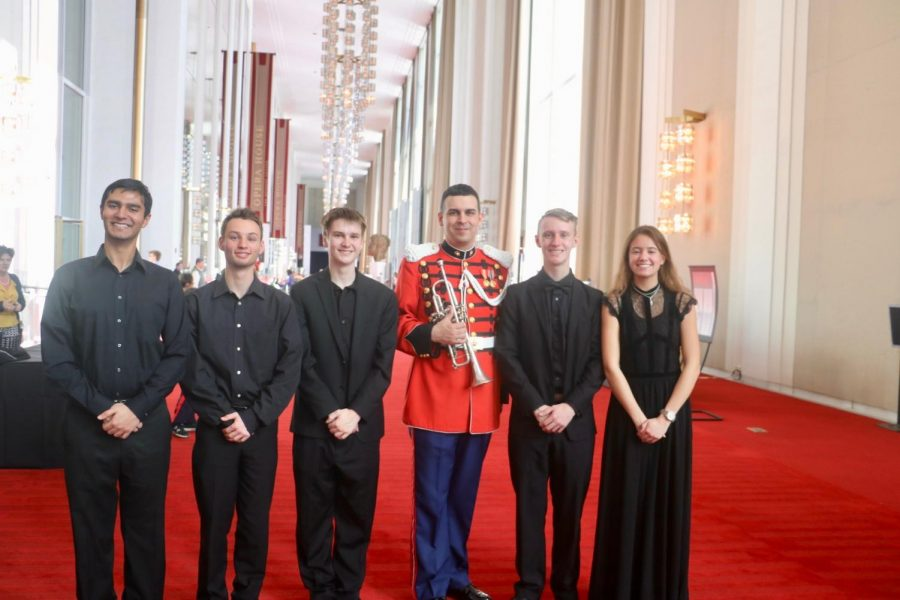 Several+band+students+pose+with+director+Cheryl+Lee+and+alum%2C+Chris+Larios%2C+who+is+now+serving+as+a+sergeant+in+the+army+and+is+a+member+of+the+US+Army+Band.
