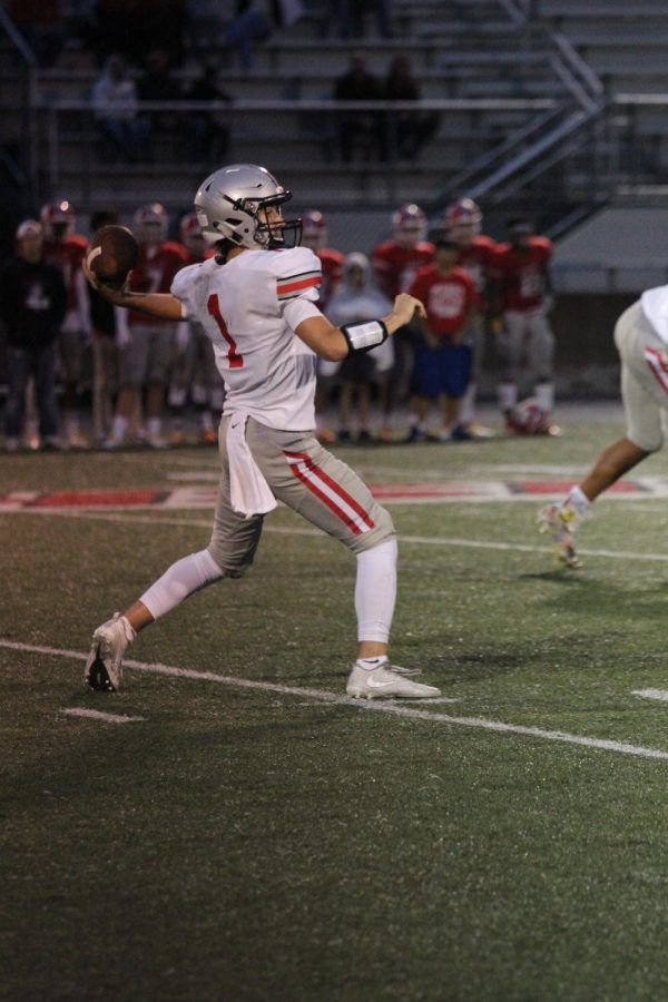 Senior Greg Riddle prepares to throw a pass through the rain at Bishop Miege on Sept. 7.