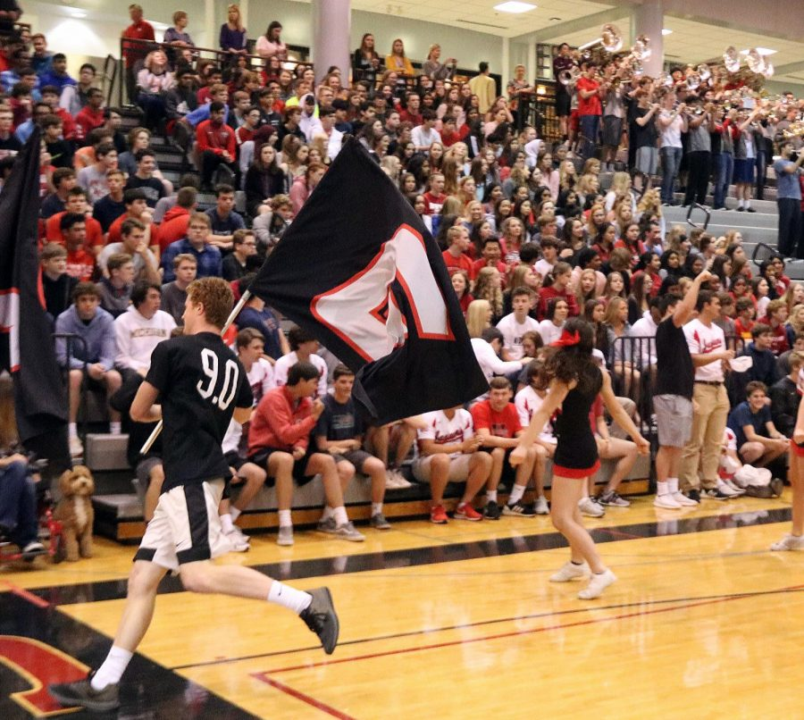 With the junior class and the pep band in the background, senior Jacob Stenslie runs around the gym as a part of the JAG FLAG crew.