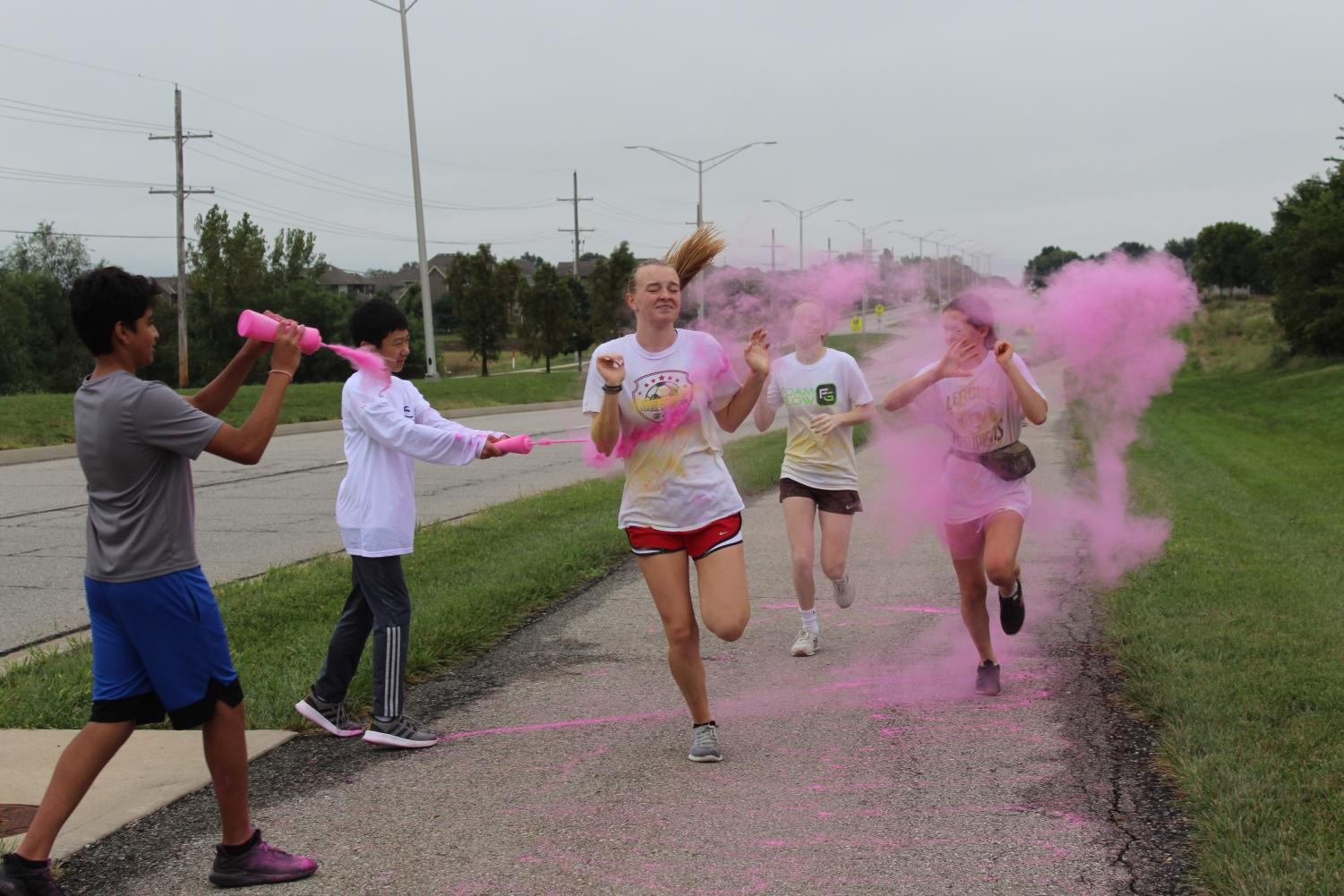 Participants in the DECA/FBBLA Color Run pass through the pink station on Sept. 26