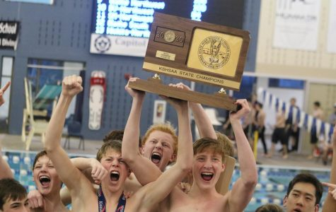 Swim team members celebrate their 6A State Championship over Olathe East on Feb. 22.