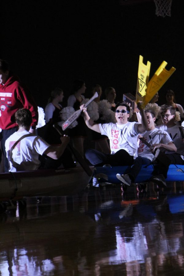 Senior Lucas Park sits in the front of a kayak depicting the Row the Boat theme as the team enters the gym for an assembly honoring their championship.