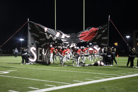 The Varsity Football team excitedly sprints through their senior night banner on Oct. 23 vs. BVNW.